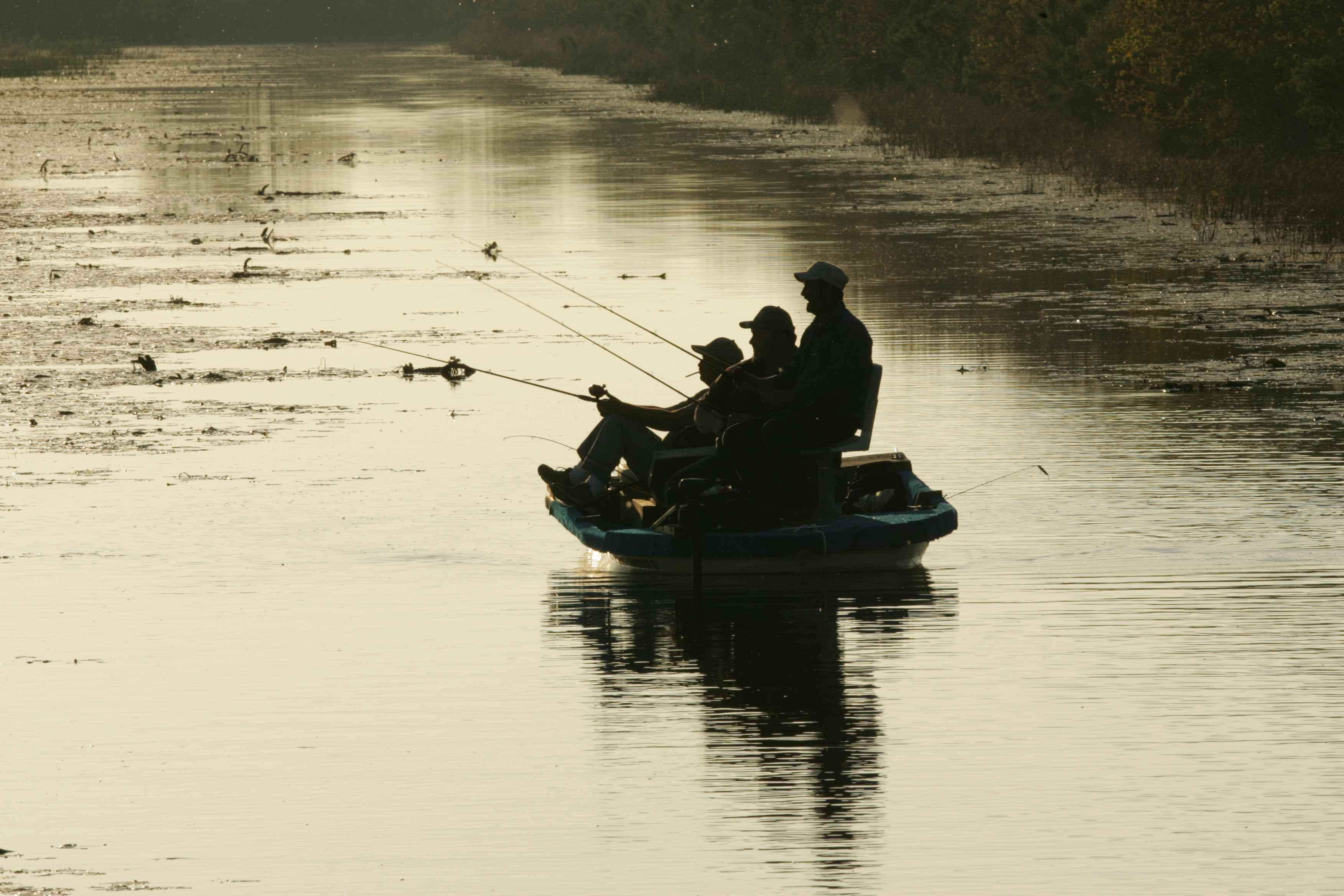 Three_men_in_silhouette_against_glassy_water_fishing_from_boat